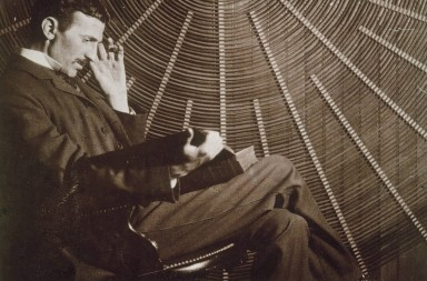 NIKOLA TESLA (1856-1943).  American electrician and inventor. Born in Croatia, of Serbian parents. Photographed, c1895, with one of his electrical generators (oscillators).